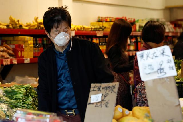 A man wears a face mask shopping at a market in the Chinatown section of San Francisco, California, U.S., February 25, 2020.   REUTERS/Shannon Stapleton