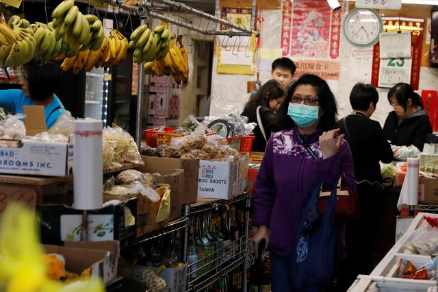 A woman wears a face mask shopping at a market in the Chinatown section of San Francisco, California, U.S., February 25, 2020.   REUTERS/Shannon Stapleton