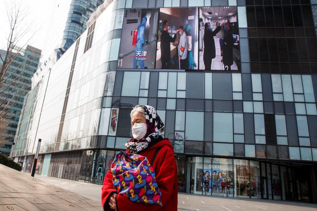 A woman wearing a face mask walks past a screen showing a video about protective measures against the new coronavirus in Beijing, China, February 26, 2020.  REUTERS/Thomas Peter