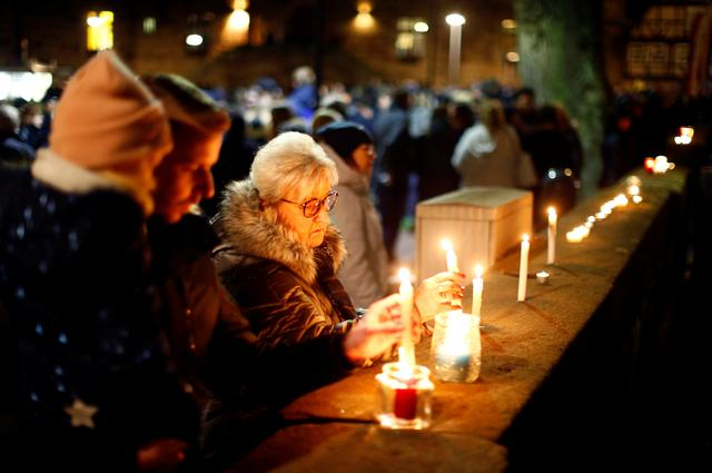 People light candles as they attend a commemoration outside a church, the day after a car ploughed into a Carnival parade, injuring several people in Volkmarsen, Germany February 25, 2020. REUTERS/Thilo Schmuelgen