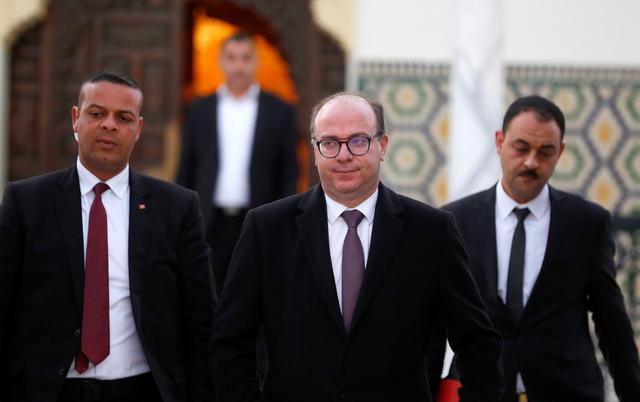FILE PHOTO: Tunisian Prime Minister Elyes Fakhfakh (C) leaves for a meeting with Tunisian President Kais Saied (not pictured) in Tunis, Tunisia February 15, 2020. REUTERS/Zoubeir Souissi