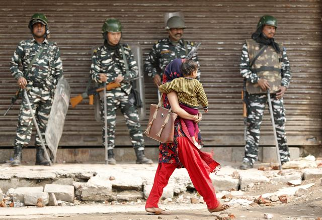 A woman carrying a child walks past security forces in a riot affected area after clashes erupted between people demonstrating for and against a new citizenship law in New Delhi, India, February 26, 2020. REUTERS/Adnan Abidi