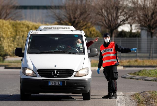 A member of the Italian Carabinieri wearing a face mask guides a driver at the entrance of the red zone of Casalpusterlengo, closed off due to a coronavirus outbreak in northern Italy, in Casalpusterlengo, Italy, February 26, 2020. REUTERS/Yara Nardi