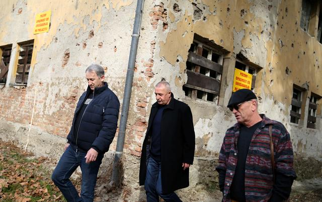 War veterans Boro Jevtic (L-R), Marko Zelic and Rizo Salkic walk past a house destroyed during the Bosnian War in Maglaj, Bosnia and Herzegovina February 23, 2020. Picture taken February 23, 2020. REUTERS/Dado Ruvic