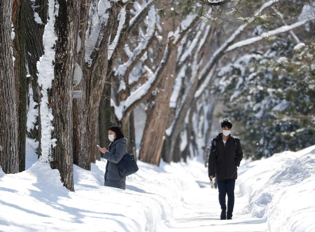 Passersby wearing protective masks walk on a snow-covered street in Sapporo, Hokkaido, Japan, February 26, 2020.  REUTERS/Issei Kato