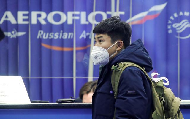 FILE PHOTO: A passenger wears a protective mask near the booking office of Russia's flagship airline Aeroflot at Sheremetyevo International Airport outside Moscow, Russia, February 4, 2020. REUTERS/Maxim Shemetov/File Photo