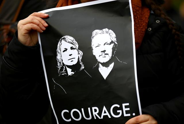 FILE PHOTO: A protester holds a sign outside Woolwich Crown Court, ahead of a hearing to decide whether Assange should be extradited to the United States, in London, Britain, February 24, 2020. REUTERS/Hannah Mckay