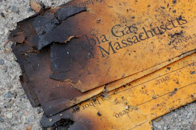 FILE PHOTO: FILE PHOTO: A burnt Columbia Gas of Massachusetts envelope sits on the sidewalk outside a home burned during a series of gas explosions in Lawrence, Massachusetts, U.S., September 14, 2018.   REUTERS/Brian Snyder/File Photo