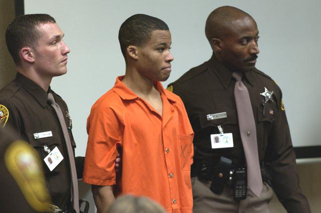 FILE PHOTO: Sniper suspect Lee Boyd Malvo, 18, is surrounded by deputies as he is brought into court to be identified by a witness during the trial of sniper suspect John Allen Muhammad at the Virginia Beach Circuit Court in Virginia Beach, Virginia, U.S., October 22, 2003. Malvo was 17 at the time of the shootings. REUTERS Davis Turner/POOL