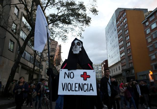 """FILE PHOTO: A demonstrator holds a placard reading """"No Violence"""" during a protest march as a national strike continued in Bogota, Colombia, November 25, 2019. REUTERS/Luisa Gonzalez/File Photo"""