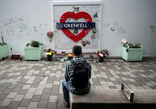 FILE PHOTO: A man looks at a hoarding covered in messages of condolence at the base of Grenfell tower two years after the fire in London, Britain, June 14, 2019. REUTERS/Hannah McKay/File Photo