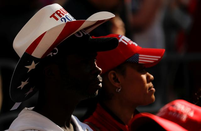 FILE PHOTO: Black supporters of U.S. President Donald Trump wearing Trump cowboy and baseball hats stand in line with other Trump supporters waiting to attend the president's campaign rally at the Las Vegas Convention Center in Las Vegas, Nevada, U.S., February 21, 2020. REUTERS/Patrick Fallon/File Photo