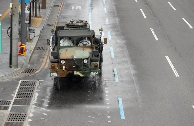 A military vehicle disinfects a street in Daegu, South Korea, February 27, 2020.    Yonhap via REUTERS