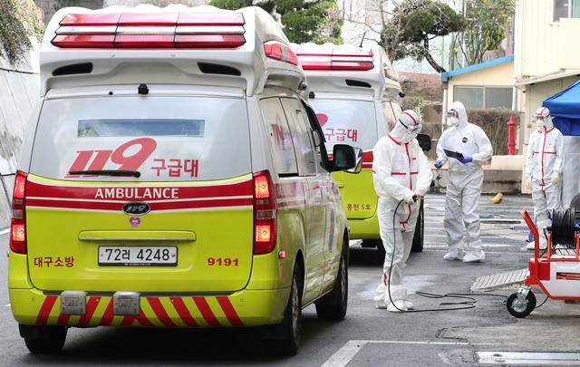 Medical workers wearing protective gear stand by outside a hospital in Daegu, South Korea, February 26, 2020.    Yonhap via REUTERS