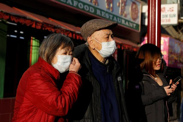 People wearing face masks walk through the Chinatown section of San Francisco, California, U.S., February 26, 2020.   REUTERS/Shannon Stapleton