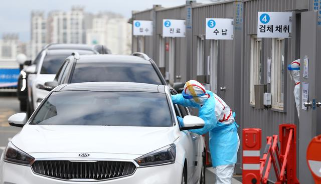 A driver gets a coronavirus test at a drive-through clinic at a hospital in Daegu, South Korea, February 27, 2020.    Yonhap via REUTERS