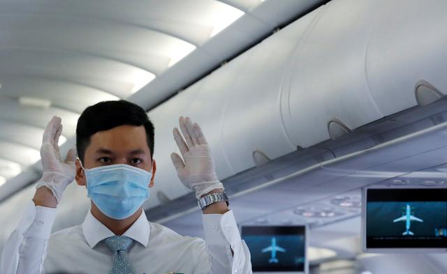 FILE PHOTO: An attendant wearing a protective mask guides the flight safety procedures before take off of a Vietnam Airlines flight, following an outbreak of the novel coronavirus, at Danang airport in Danang city, Vietnam February 23, 2020. REUTERS/Kham