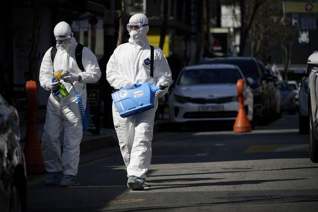 Employees from a disinfection service company sanitize a shopping district in Seoul, South Korea, February 27, 2020.   REUTERS/Kim Hong-Ji