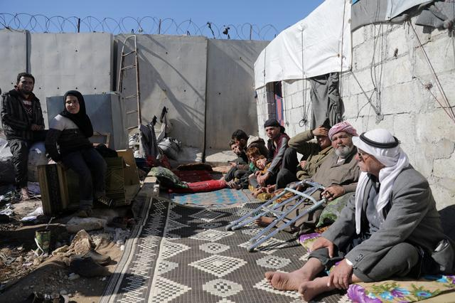 FILE PHOTO: An internally displaced Syrian family sit together outside a tent near the wall in Atmah IDP camp, located near the border with Turkey, Syria February 26, 2020. REUTERS/Khalil Ashawi/File Photo