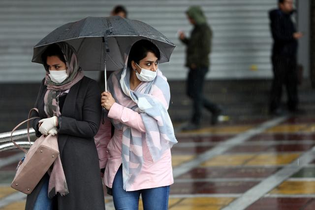 Iranian women wear protective masks to prevent contracting coronavirus, as they walk in the street in Tehran, Iran February 25, 2020. WANA (West Asia News Agency)/Nazanin Tabatabaee via REUTERS