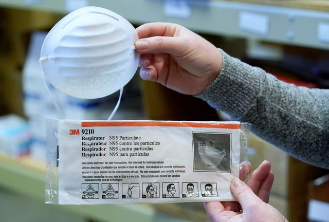 FILE PHOTO: A standard dust & particle mask, and an N95 medical respirator mask (bottom), that are part of personal protection and survival equipment kits ordered by customers preparing against novel coronavirus, are seen at Nitro-Pak in Midway, Utah, U.S. February 27, 2020.  REUTERS/George Frey