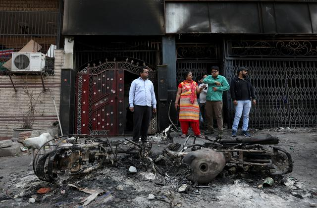 FILE PHOTO: People stand next to the wreckage of motorcycles that were set on fire by a mob in a riot affected area after clashes erupted between people demonstrating for and against a new citizenship law in New Delhi, India, February 26, 2020. REUTERS/Rupak De Chowdhuri/File Photo
