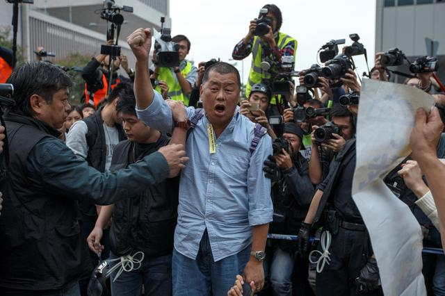 FILE PHOTO: Tycoon and Apple Daily Newspaper owner Jimmy Lai shouts slogan before he is taken away by police officer at an area previously blocked by pro-democracy supporters, outside the government headquarters in Hong Kong, December 11, 2014. REUTERS/Athit Perawongmetha