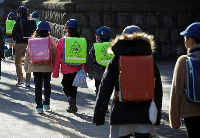 Elementary school students walk toward their school in Tokyo, Japan, February 28, 2020.  REUTERS/Issei Kato