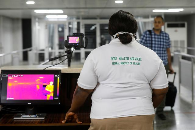 FILE PHOTO: An official monitors thermal scanners as a passenger walks past upon arrival of a flight into Lagos, Nigeria January 22, 2020. REUTERS/Temilade Adelaja