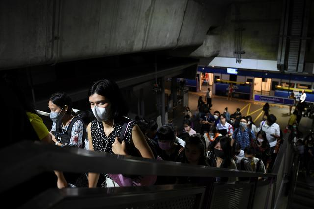 FILE PHOTO: Commuters wearing protective masks walk inside the Skytrain BTS in Bangkok, Thailand February 24, 2020. REUTERS/Chalinee Thirasupa
