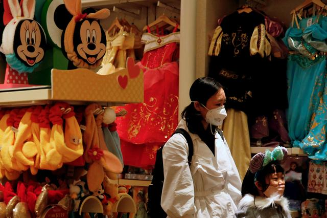FILE PHOTO: A child wears mask as she tries a themed ears at a souvenir shop in Disneyland hotel after Hong Kong Disneyland that has been closed, following the coronavirus outbreak in Hong Kong, China January 26, 2020. REUTERS/Tyrone Siu/File Photo