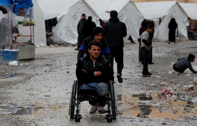 FILE PHOTO: Internally displaced Syrian is pushed in a wheelchair along the tents in an IDP camp located in Idlib, Syria February 27, 2020.  REUTERS/Umit Bektas