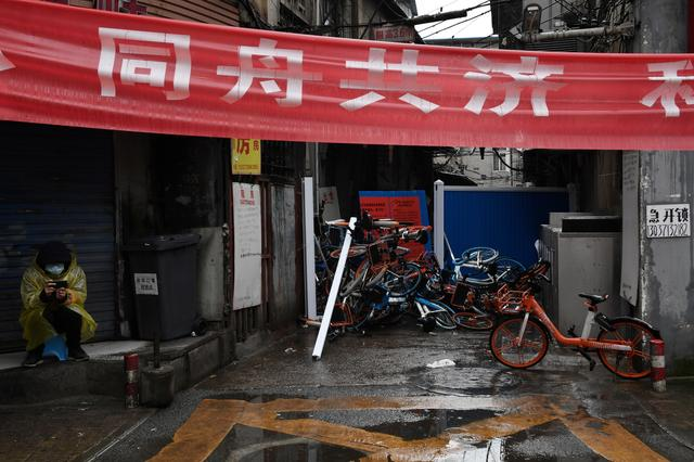 A volunteer keeps watch near an entrance blocked by barricades and shared bicycles at a residential area in Wuhan, the epicentre of the novel coronavirus outbreak, Hubei province, China February 28, 2020. REUTERS/Stringer  CHINA OUT.
