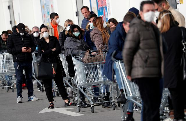 FILE PHOTO: People queue at a supermarket outside the town of Casalpusterlengo, which has been closed by the Italian government due to a coronavirus outbreak in northern Italy, February 23, 2020. REUTERS/Guglielmo Mangiapane/File Photo