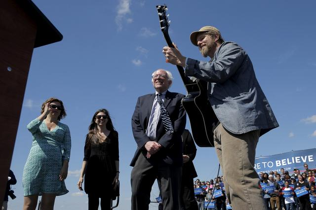 """FILE PHOTO: U.S. Democratic presidential candidate and U.S. Senator Bernie Sanders listens as Guy Forsyth (R), Cathy Guthrie, granddaughter of Woody Guthrie (L) and Amy Nelson, daughter of Willie Nelson, perform """"This Land Is Your Land"""" at a campaign rally in Austin, Texas, February 27, 2016.  REUTERS/Brian Snyder/File Photo"""