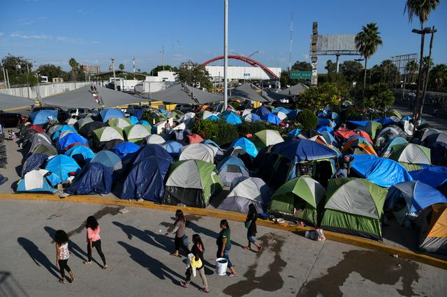 """FILE PHOTO: Migrants, most of them asylum seekers sent back to Mexico from the U.S. under the """"Remain in Mexico"""" program officially named Migrant Protection Protocols (MPP), occupy a makeshift encampment in Matamoros, Tamaulipas, Mexico, October 28, 2019. REUTERS/Loren Elliott/File Photo"""