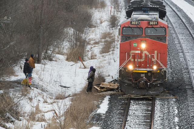 A Canadian National Railway (CN Rail) train moves through wooden pallets placed there by occupants of a Tyendinaga Mohawk Territory encampment set up in support of the Wet'suwet'en Nation who are trying to stop construction of British Columbia's Coastal GasLink pipeline, in Tyendinaga, Ontario, Canada February 26, 2020.   REUTERS/Alex Filipe