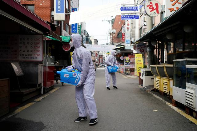 FILE PHOTO: Employees from a disinfection service company sanitize a traditional market in Seoul, South Korea, February 26, 2020.   REUTERS/Kim Hong-Ji