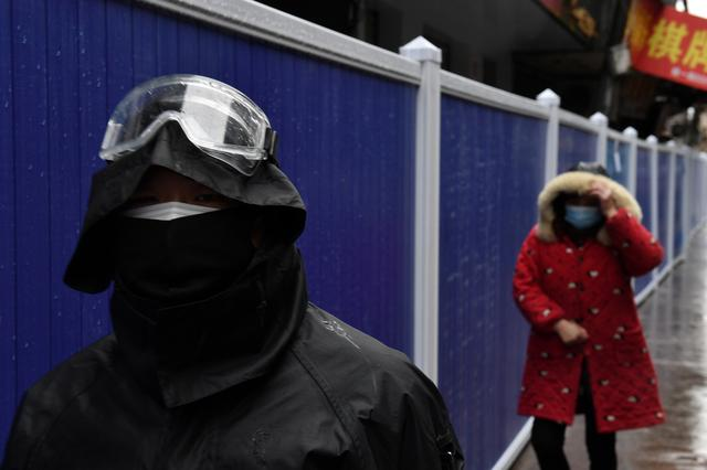 People wearing face masks walk next to barriers set up at a residential area in Wuhan, the epicentre of the novel coronavirus outbreak, Hubei province, China February 28, 2020. REUTERS/Stringer