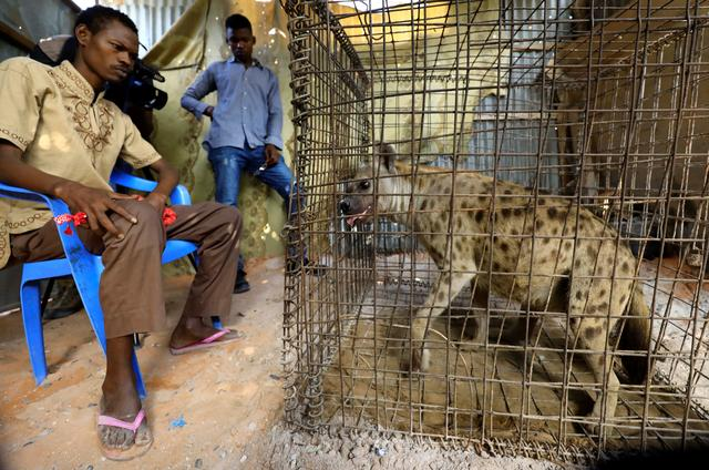 Mohamed Sheikh Yakub, a patient suffering with mental illness, sits inside the treatment room where a hyena believed to exorcise evil spirits that cause mental illness is secured in a cage, in Hodan district of Mogadishu, Somalia February 15, 2020. Picture taken February 15, 2020. REUTERS/Feisal Omar