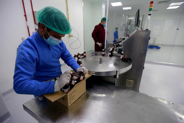 FILE PHOTO: Workers inspect the production line at the privately owned Modern Company for Drug Industries (MDI) factory in the town of Abu Ghraib, Iraq, April 13, 2019. REUTERS/Alaa al-Marjani