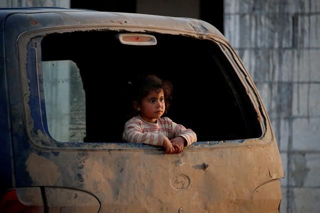 FILE PHOTO: An internally displaced Syrian girl inspects outside from a broken window of a van in an IDP camp near Idlib, Syria February 27, 2020. REUTERS/Umit Bektas/File photo