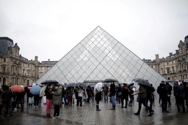 FILE PHOTO: Tourists queue to enter the Louvre as the staff closed the museum during a staff meeting about the coronavirus outbreak, in Paris, France, March 2, 2020. REUTERS/Benoit Tessier