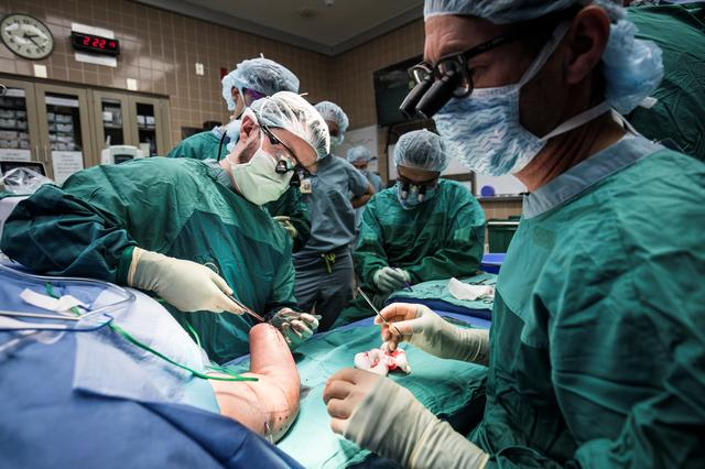 Paul Cederna (foreground), the Robert Oneal Professor of Plastic Surgery at the University of Michigan, shifts his attention as Daniel Lyons, a resident of plastic surgery, stitches up the arm of Karen Sussex, a participant in the U-M RPNI study, after implanting clinical bipolar electrodes that enable intuitive mind control of an advanced prosthetic handin Ann Arbor, Michigan, October 24, 2018. Evan Dougherty/University of Michigan Engineering via REUTERS