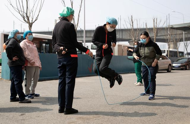 Medical workers wearing face masks jump rope as they take a break outside the hotel where they stay, in Wuhan, the epicentre of the novel coronavirus outbreak, Hubei province, China March 5, 2020. China Daily via REUTERS