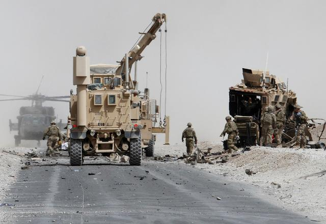 FILE PHOTO: U.S. troops assess the damage to an armoured vehicle of NATO-led military coalition after a suicide attack in Kandahar province, Afghanistan August 2, 2017. REUTERS/Ahmad Nadeem