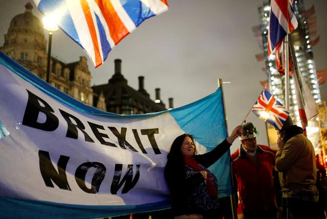 FILE PHOTO: A woman waves a British flag on Brexit day in London, Britain January 31, 2020. REUTERS/Henry Nicholls