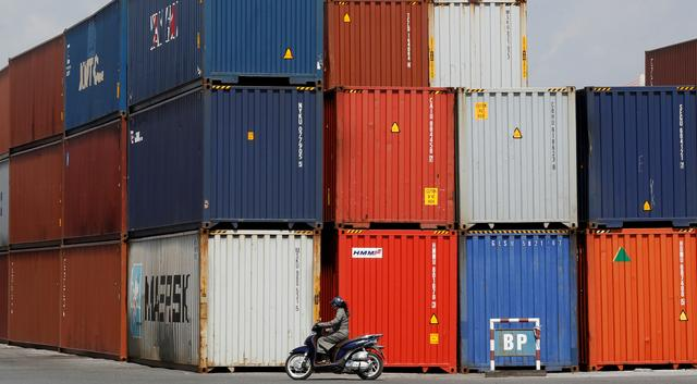 FILE PHOTO: A woman rides a motorcycle as she passes containers at Hai Phong port, Vietnam September 25, 2018. REUTERS/Kham/File Photo