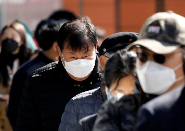 People wearing face masks stand in line to buy masks at a post office amid the rise in confirmed cases of coronavirus disease (COVID-19) in Daegu, South Korea, March 5, 2020. REUTERS/Kim Kyung-Hoon