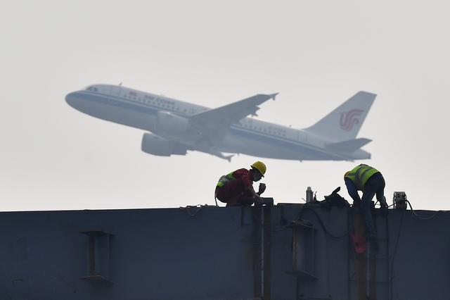 FILE PHOTO: An Air China plane flies past workers labouring at the construction site of an exhibition centre in Chengdu, Sichuan province, China February 26, 2020. China Daily via REUTERS